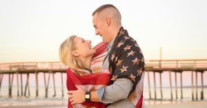 A military couple poses with the American flag