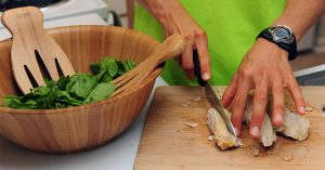 A person slicing chicken on a cutting board