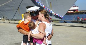 Sailor hugging family after getting off boat