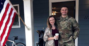 military spouse standing with service member outside home