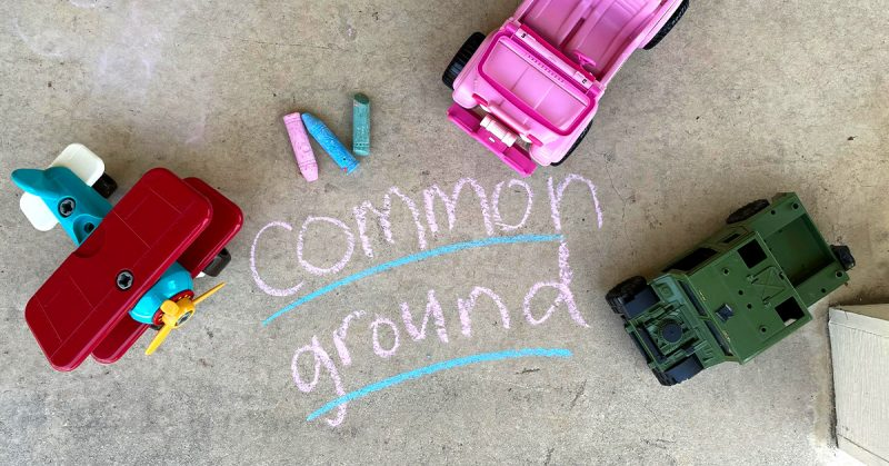 """An aerial view of pavement with the words """"Common Ground"""" written on it in sidewalk chalk."""