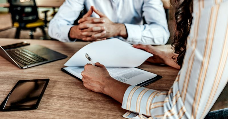 A photo of 2 people having a meeting, with a below-neck view. One is writing things down on a notepad and one has their hands crossed.