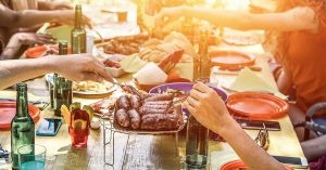A table is set with food and place settings and hands are seen serving food. It is sunset.