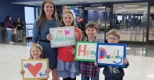 A family posing with signs at the airport