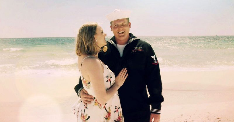 Service member and spouse smiling on the beach