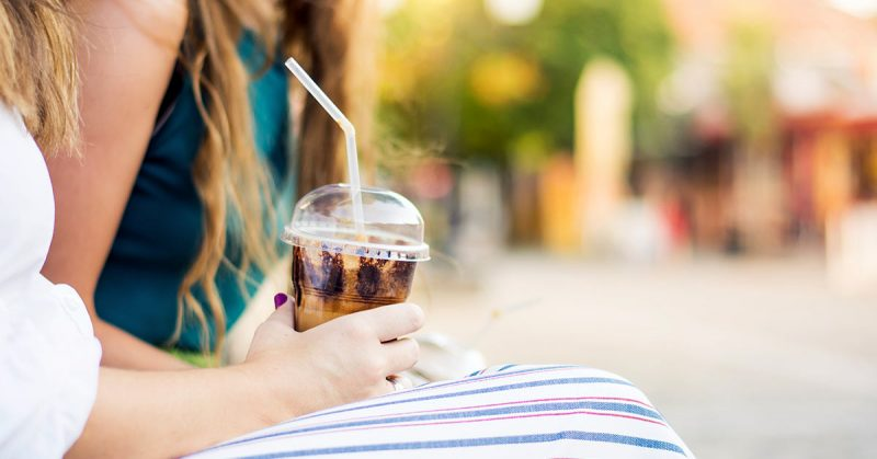 A woman holding an iced coffee