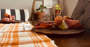 """A view of a Thanksgiving table is shown, featuring an orange plaid blanket, a pumpkin table-setting and a sign that says """"thankful."""""""