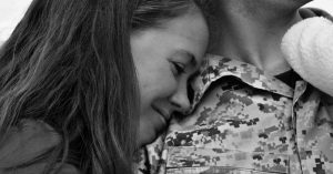 A black and white picture of a woman leaning on a service member's chest.
