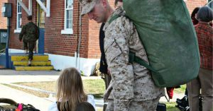 2. A service member in uniform holds hands with a little girl. He wears a pack.