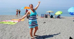 1. MilSpouse Lizann poses for the camera on a beach with the ocean in the background.