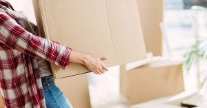 A neck-down view of a woman in a flannel shirt carrying a moving box.