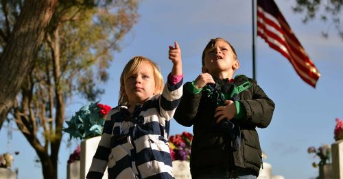 1. A female child and a male child are seen pointing at the camera. In the background, an American flag flies.