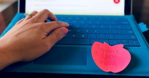 """A hand is seen typing on a laptop. A sticky note on the laptop reads """"Support a click away…"""""""