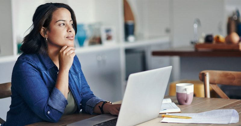 A woman gazes into the distance, thinking, as she works at a laptop that is open on a kitchen island.