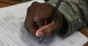 hand holding pen writing on paper
