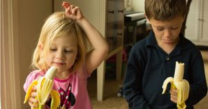 Two kids each holding a banana