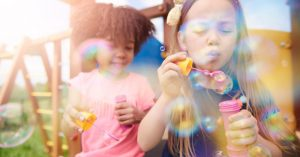 Two children blowing bubbles