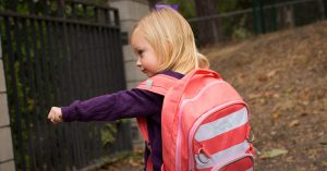 A young girl wearing a pink backpack making a fist