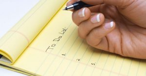 A person writing a to-do list in a yellow notepad