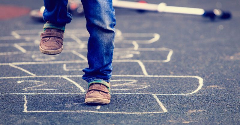 Closeup of a kid's feet playing hopscotch