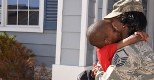 Service member hugging child