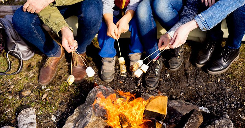 A group of people sitting around the campfire roasting marshmallows