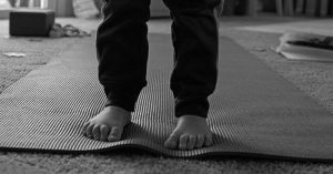 A closeup of a child's feet standing on a yoga mat