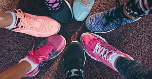 Closeup of people's feet wearing colorful running shoes arranged in a circle