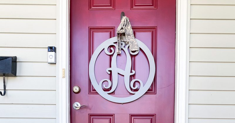 A photograph of a red front door with a decoration hanging on the front