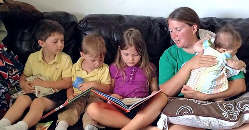 A woman and four children reading on a couch