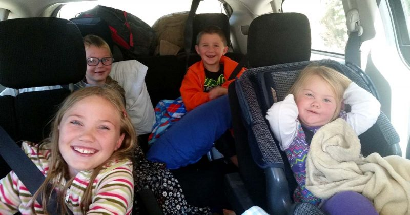 Four kids smile for the camera in a car that is loaded up with pillows and bags for a roadtrip.