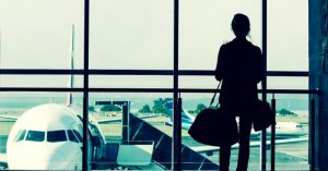 Silhouette of a woman standing in front of a window in an airport