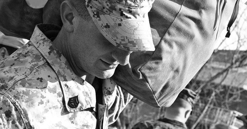 A closeup of a service member holding his pack
