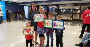 family at the airport holding up welcome home signs for their service member