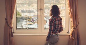 young woman standing and looking out a window