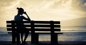 Lonely woman sitting alone on a bench