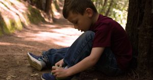 A boy sitting next to a tree tying his shoelaces