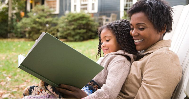 A happy mother and daughter reading a book together