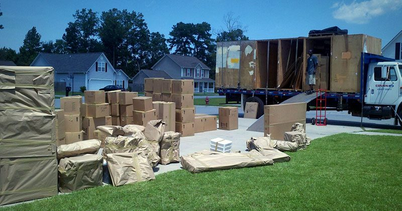 Large amount of boxes piled in a driveway with a large moving truck in the background