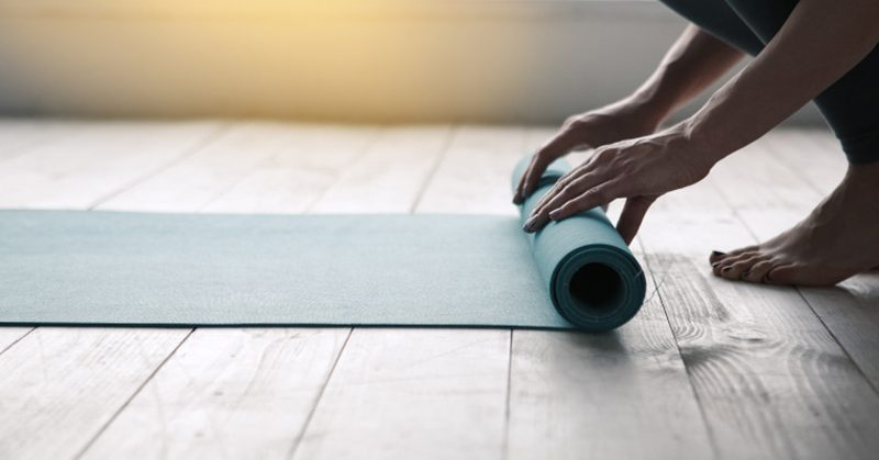 Closeup of a woman rolling up a yoga mat