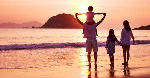 Family enjoying the beach during sunset