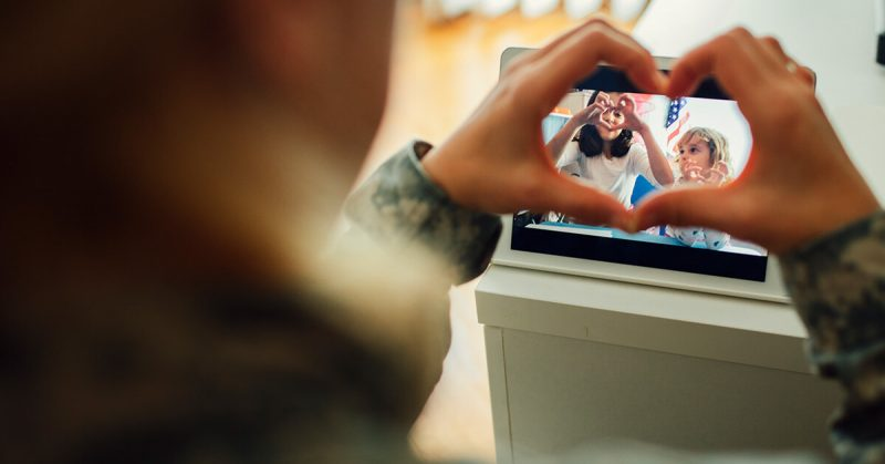 service member makes heart with fingers while facetiming