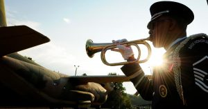 Closeup of a service member playing a bugle