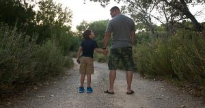 Father and son holding hands on a walking trail
