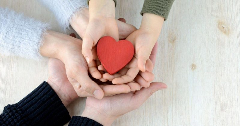 Three pairs of hands holding a heart