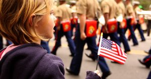 small girl holds american flag at parade
