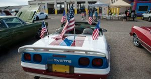 A white corvette decorated with many American flags