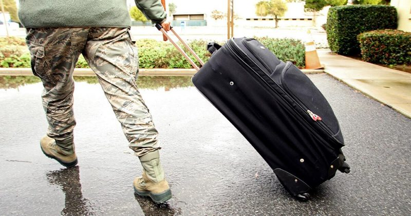 Service member pulling a suitcase