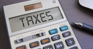 Closeup of a calculator with the word TAXES displayed on the screen
