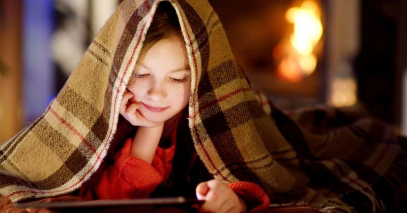 Young girl under a blank reading a tablet